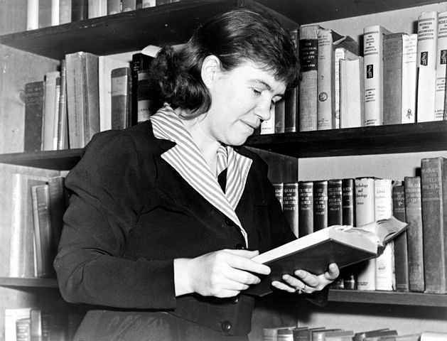 Black-and-white photo from 1950 of Margaret Mead before a bookcase, reading a book