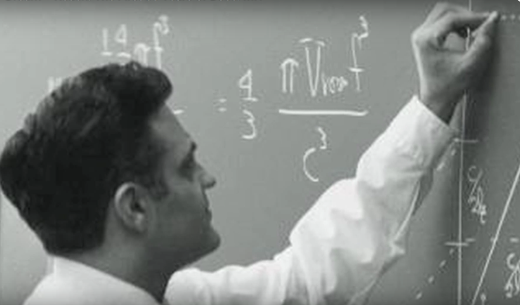 Black-and-white still from video showing Amar Bose writing on a blackboard
