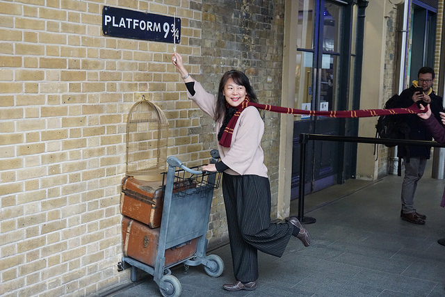 "Smiling East Asian girl near a wall with a sign that says ""Platform 9 3/4"" and half a luggage trolley sticking out of the wall"