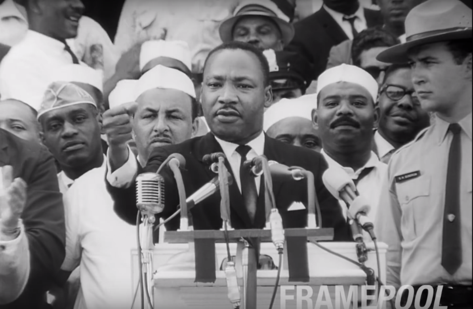 Black-and-white image of Martin Luther King, Jr., giving his famous 'I have a dream' speech in 1963, cheered on by supporters in Gandhi caps